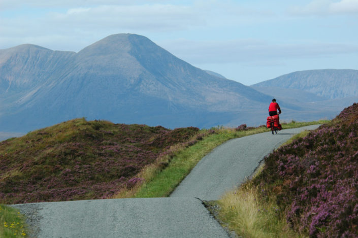 A touring cyclist crests a hill in Scotland.