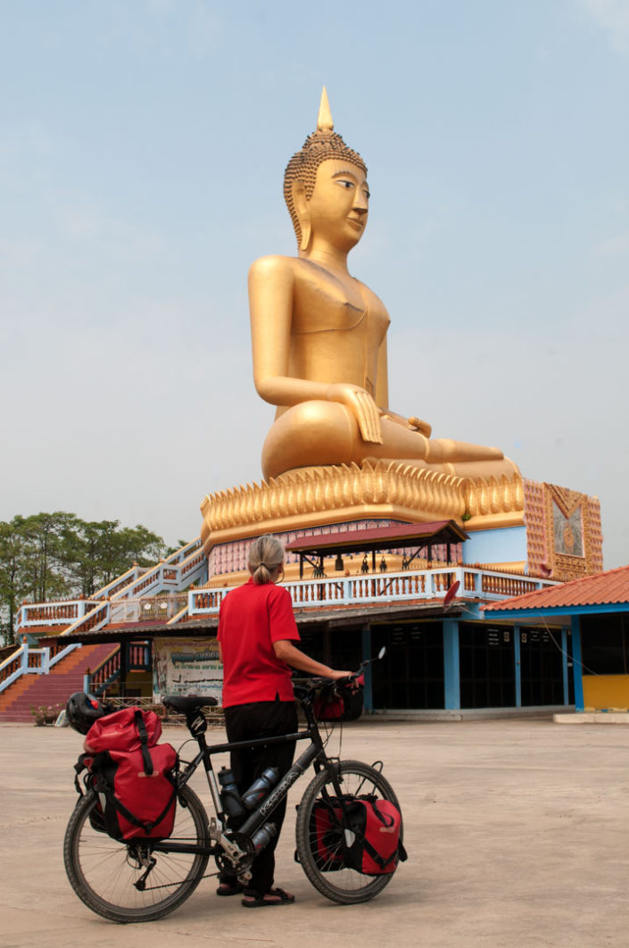 A touring bicyclist looks up at a large Buddha statue in Thailand.