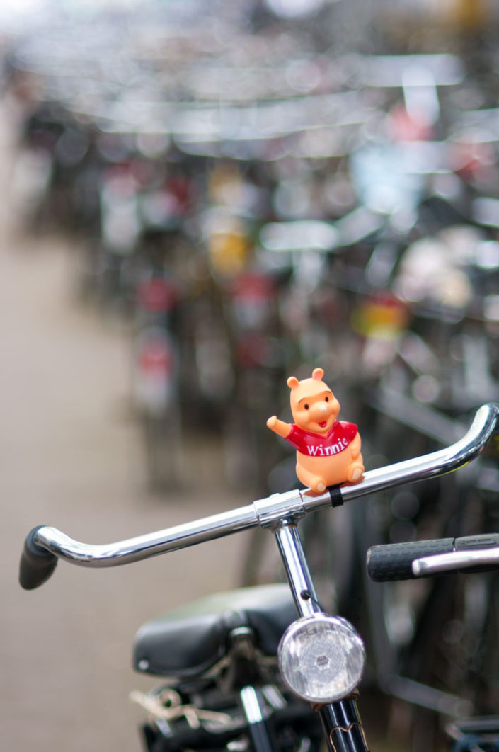 Winnie the Pooh stands on bicycle handlebars in Amsterdam.