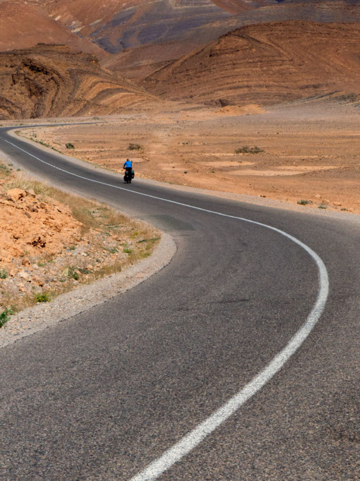 A small blue cyclist heads down a windy road in the Moroccan desert.