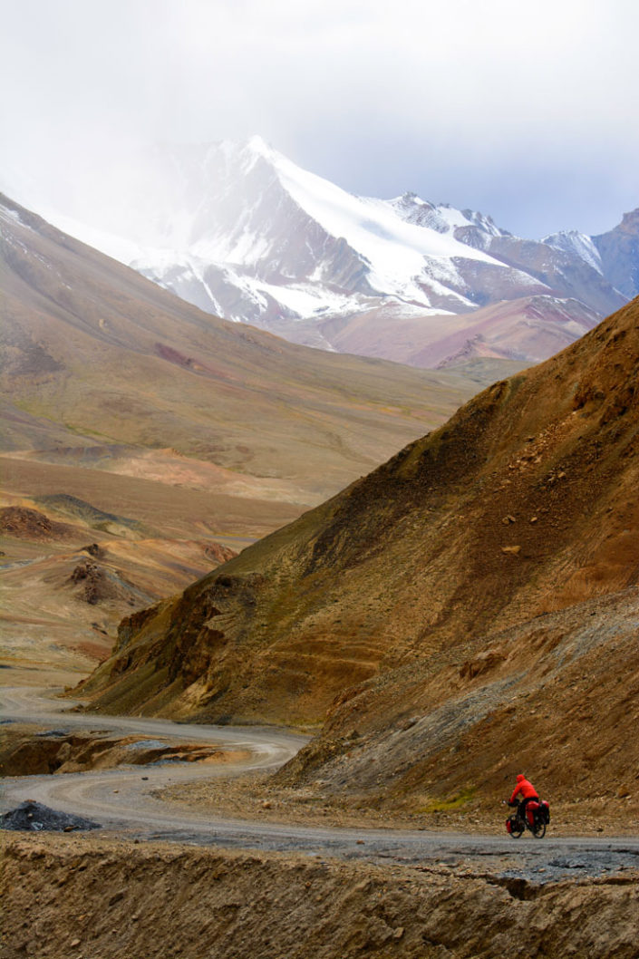 A red bike heads down Ak Baital pass on the Pamir highway.