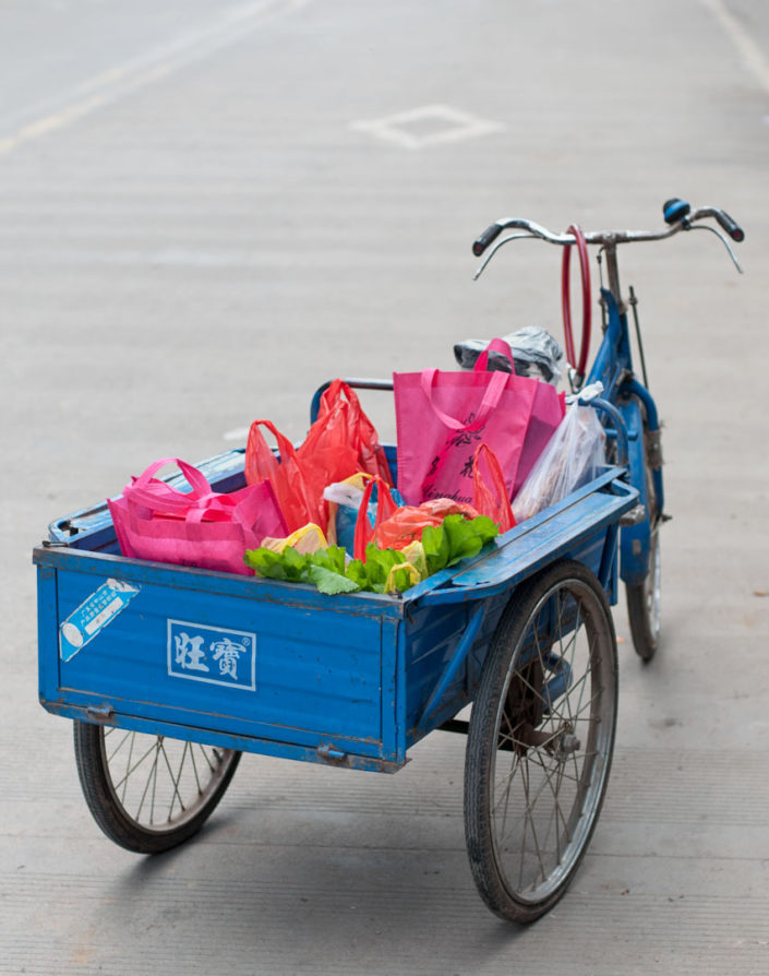 A blue Chinese cargo bike is full of brightly colored bags.