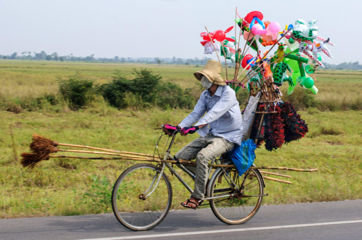 A cycling broom and balloon salesman in Cambodia.