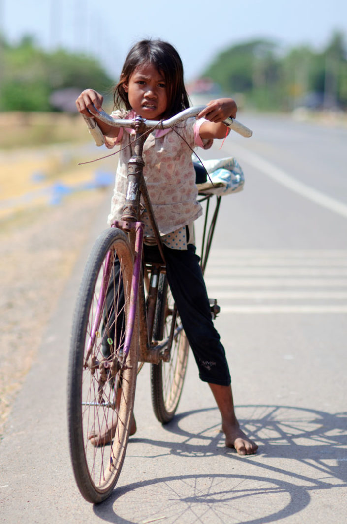 A small girl rides a bicycle in Cambodia.