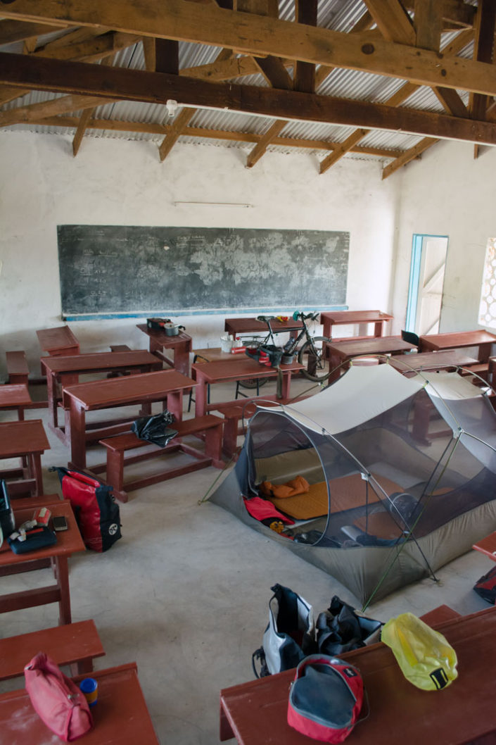 Touring cyclists camp in a School classroom in Africa.