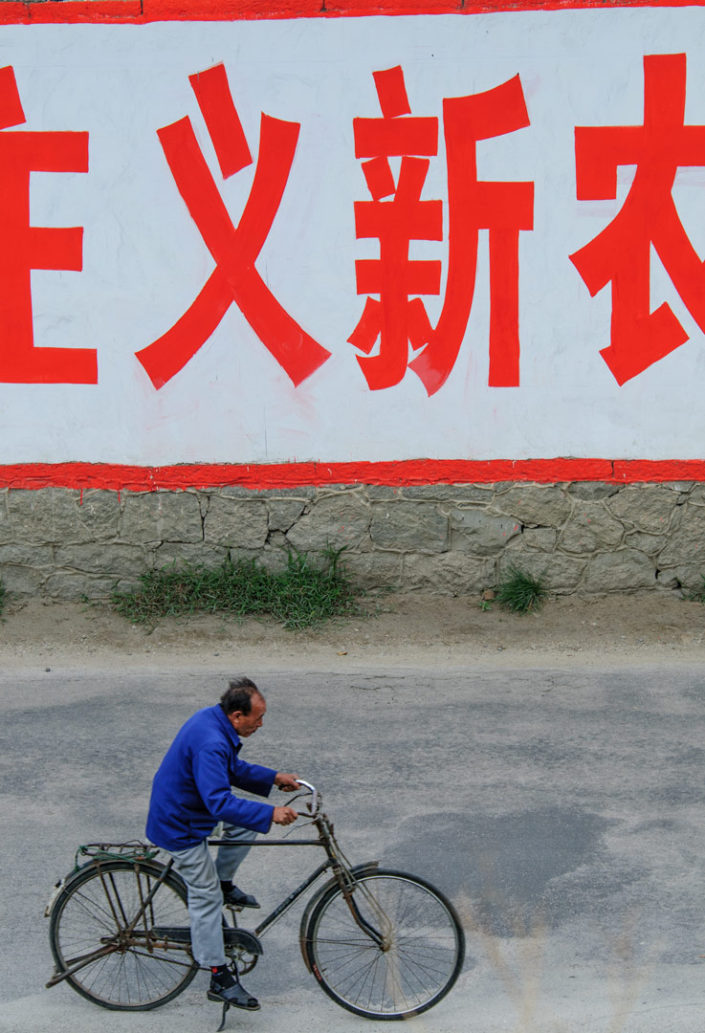 A man cycles past a sign in Chinese