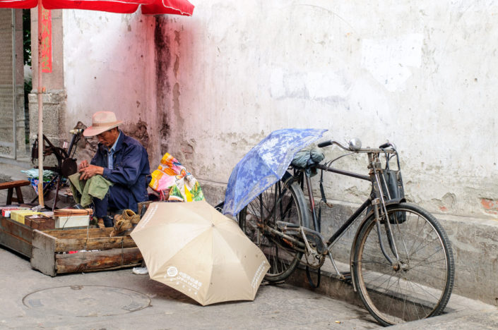 A bicycle is parked next to a shoe relpair stall in China