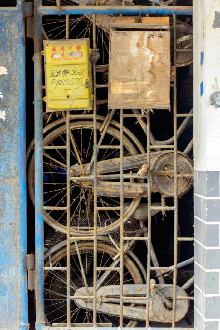 Old dusty bicycles stand behind a gate door in China