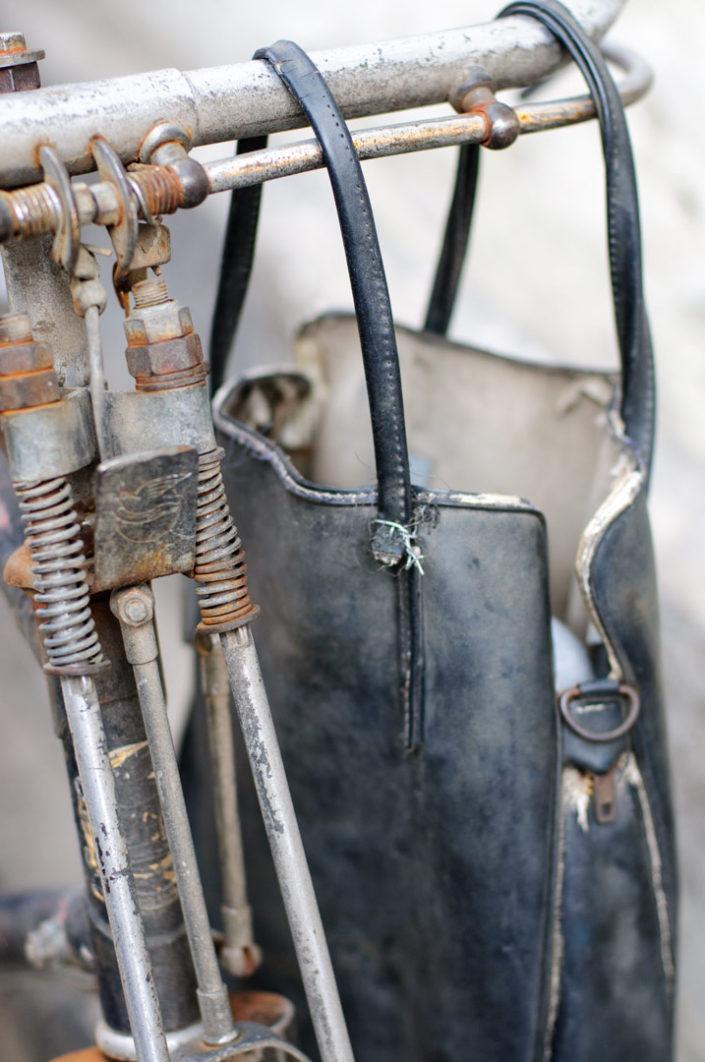 A handbag hangs from bicycle handlebars.