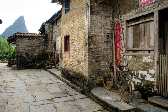 A bicycle leans against a traditional house in China