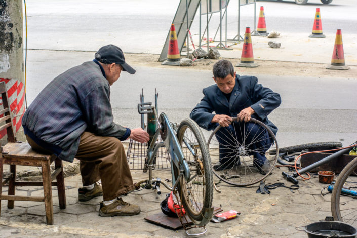 Two men fix a bicycle tire in China