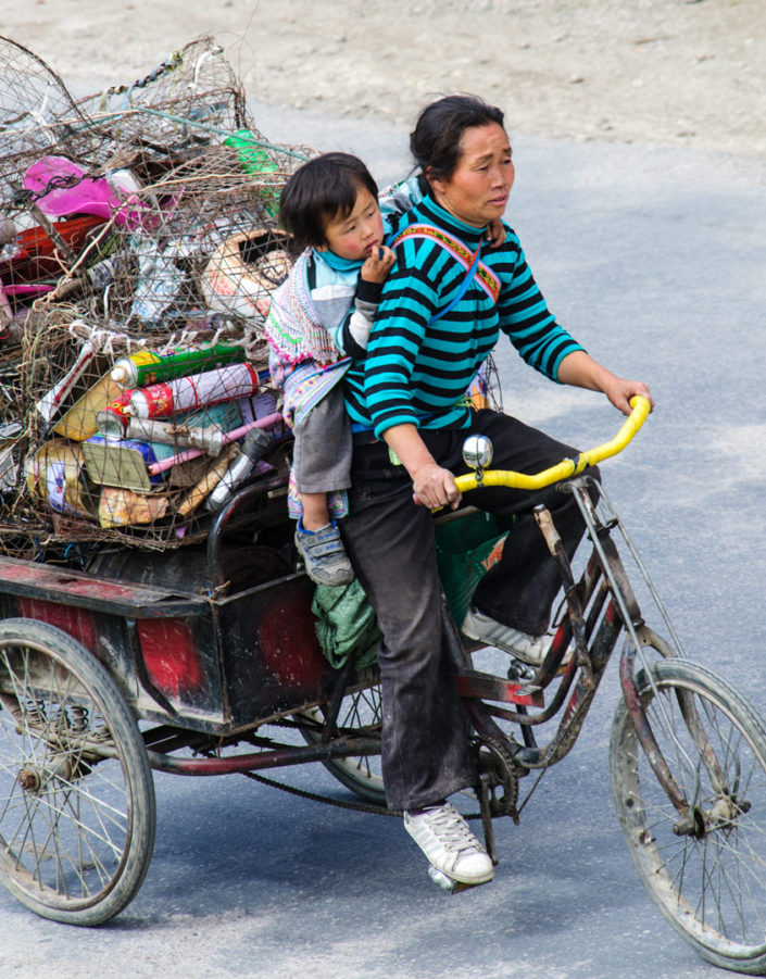 A Chinese lady pedals her cargo bike with her child attached to her bike.