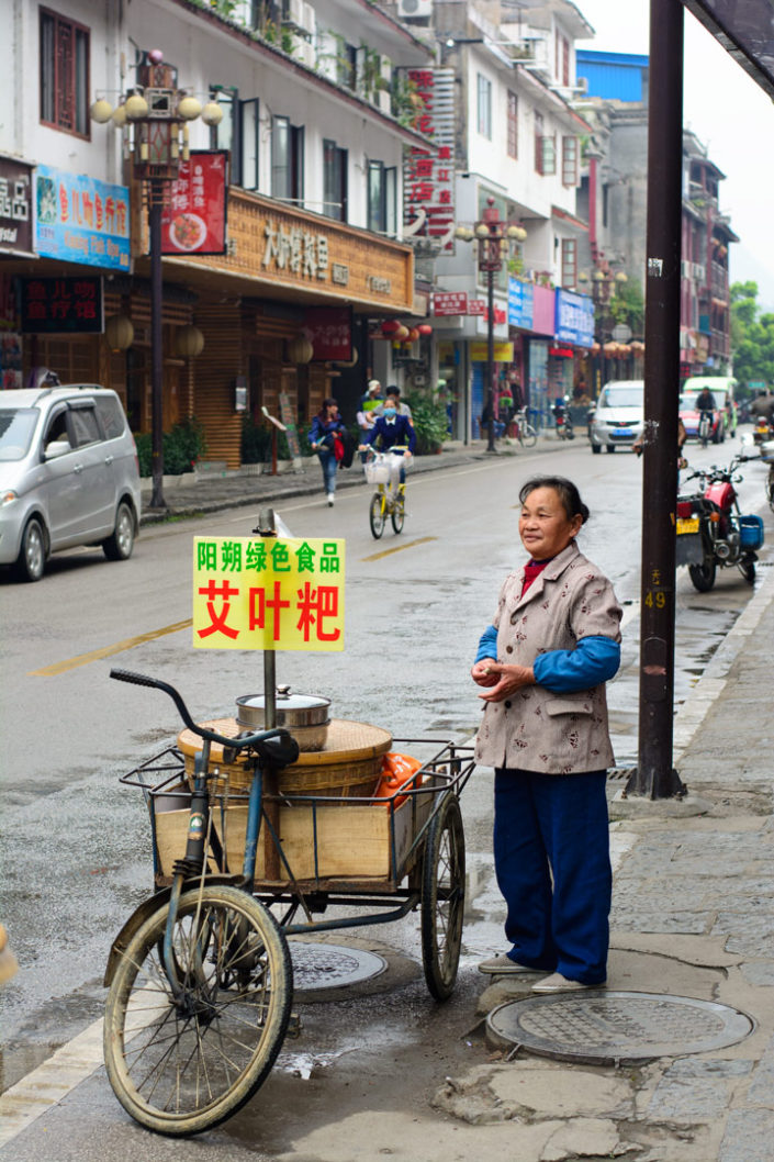 A Chinese lady sells snacks from her cargo bike in Yangshuo, China