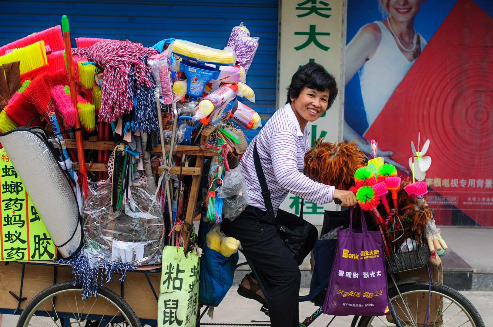 A chinese lady cycles on a cargo bike full of cleaning goods.