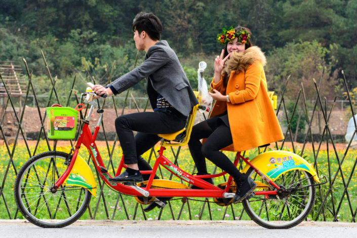 Chinese tourists pedal through the Karst mountains in China