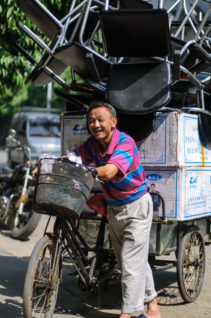 A Chinese man pushes his cargo bike that is loaded up with chairs.