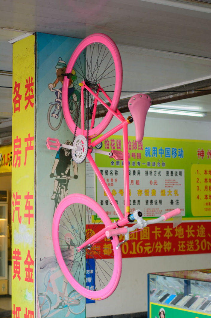 A pink single speed bicycle hangs on a wall in a Chinese shop