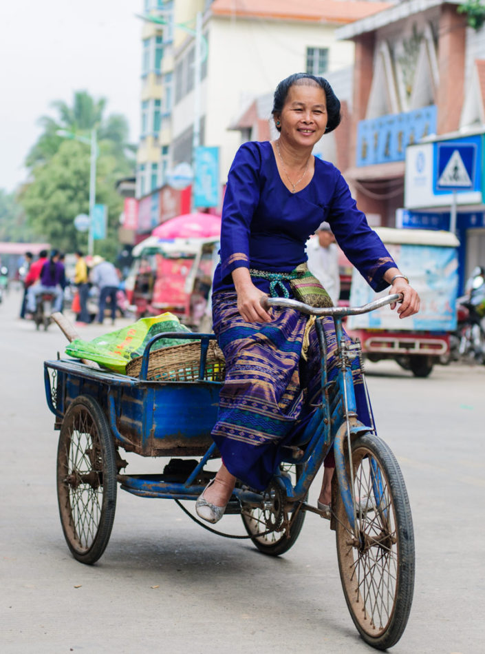 A Chinese lady cycles to the market on her cargo bike