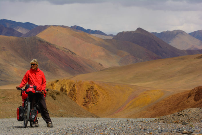 A Western touring cyclist stands on top of Ak Baital Pass in Tajikistan.