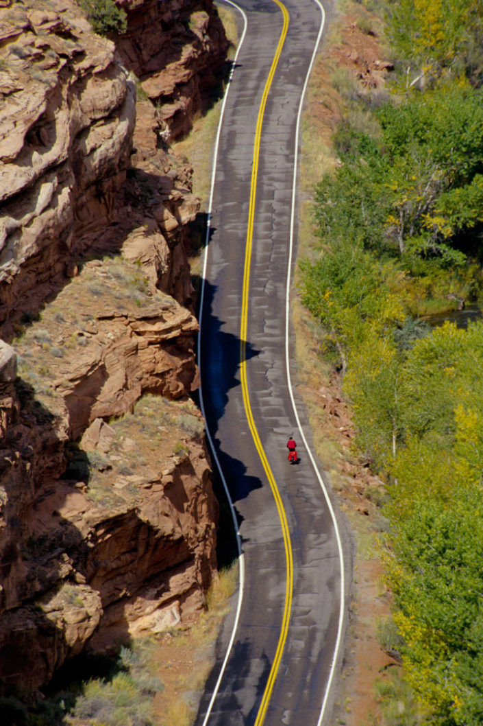 A small red cyclist rides past a rock wall in Utah.