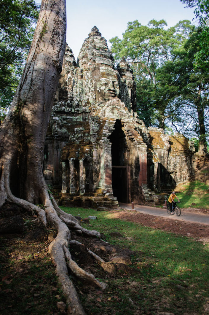 A cyclist heads through an archway in Angkor Wat Cambodia.