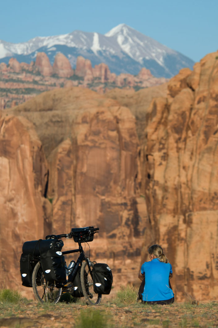 A touring cyclist gazes over rock formations near Canyonlands.