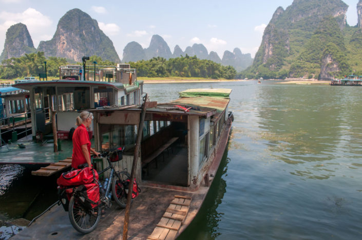 A touring cyclist takes a boat across a river near Guilin, China.