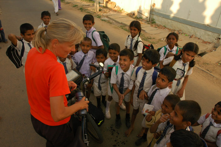 Indian school kids gather around a female touring cyclist.