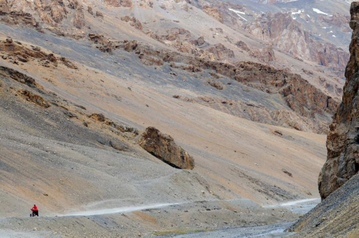 A small red bicyclist pushes their bike up a mountain pass on the Leh Manali highway.