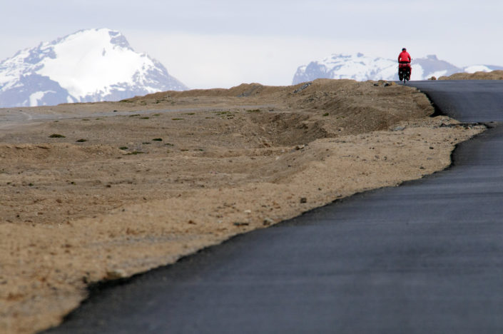 A littlre red cyclist heads across the More plains on the Leh Manali highway