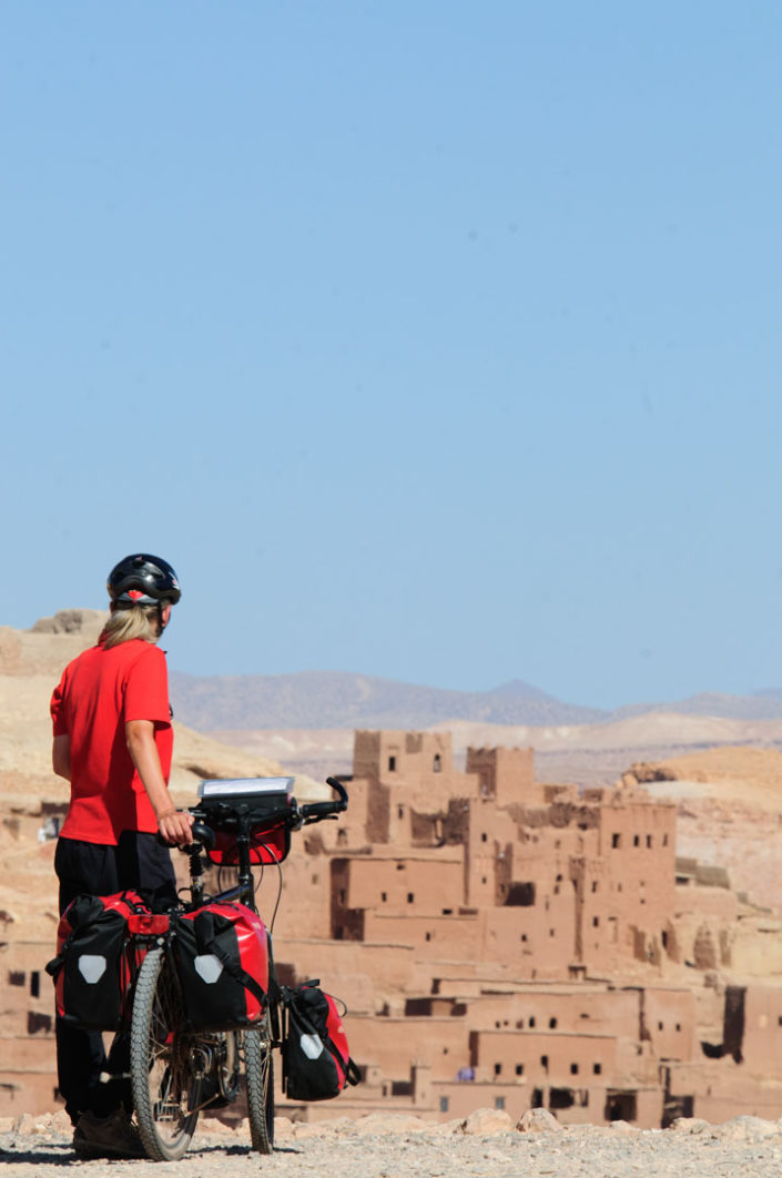 A touring cyclist looks out over Ait Ben Hadou in Morocco