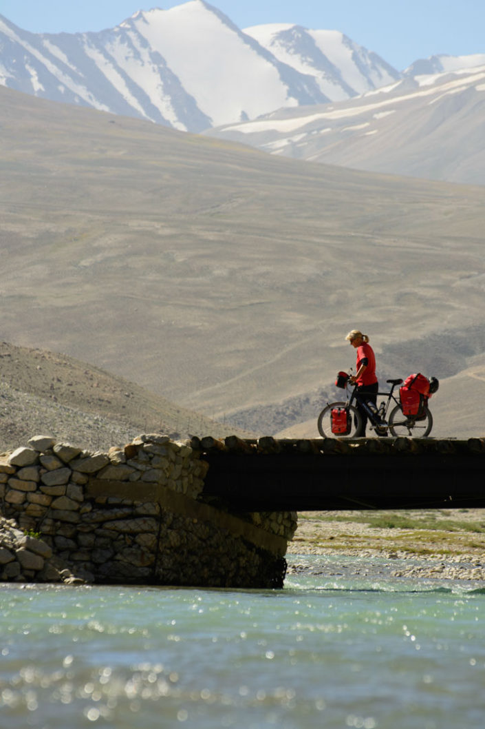 A touring cyclist stands on a bridge next to the Pamir highway.