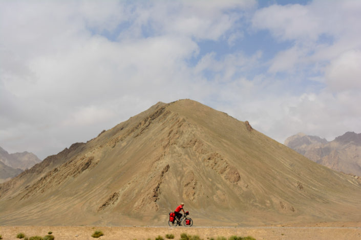 A littlle red cyclist pedals past a mountain on the Pamir highway in Tajikistan.