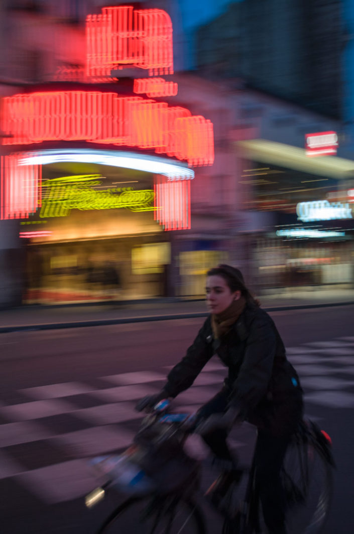 A Paris cyclist rides past a neon sign in the evening hours