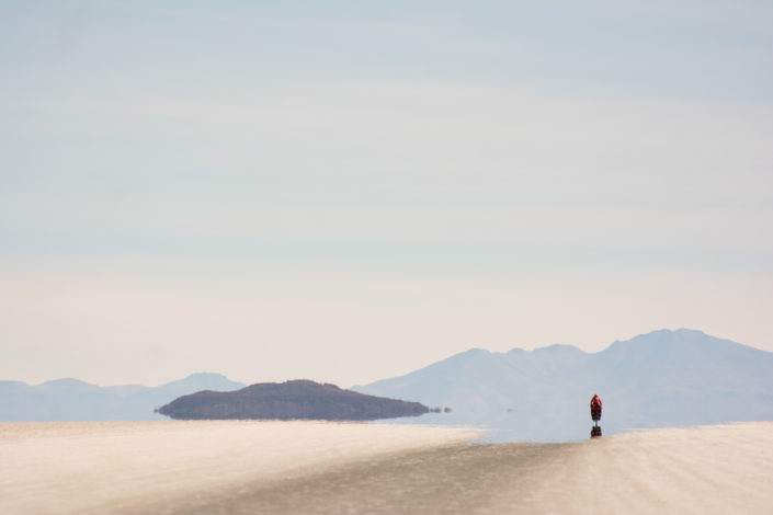 A little red bicyclist heads across the Salar de Uyuni in Bolivia