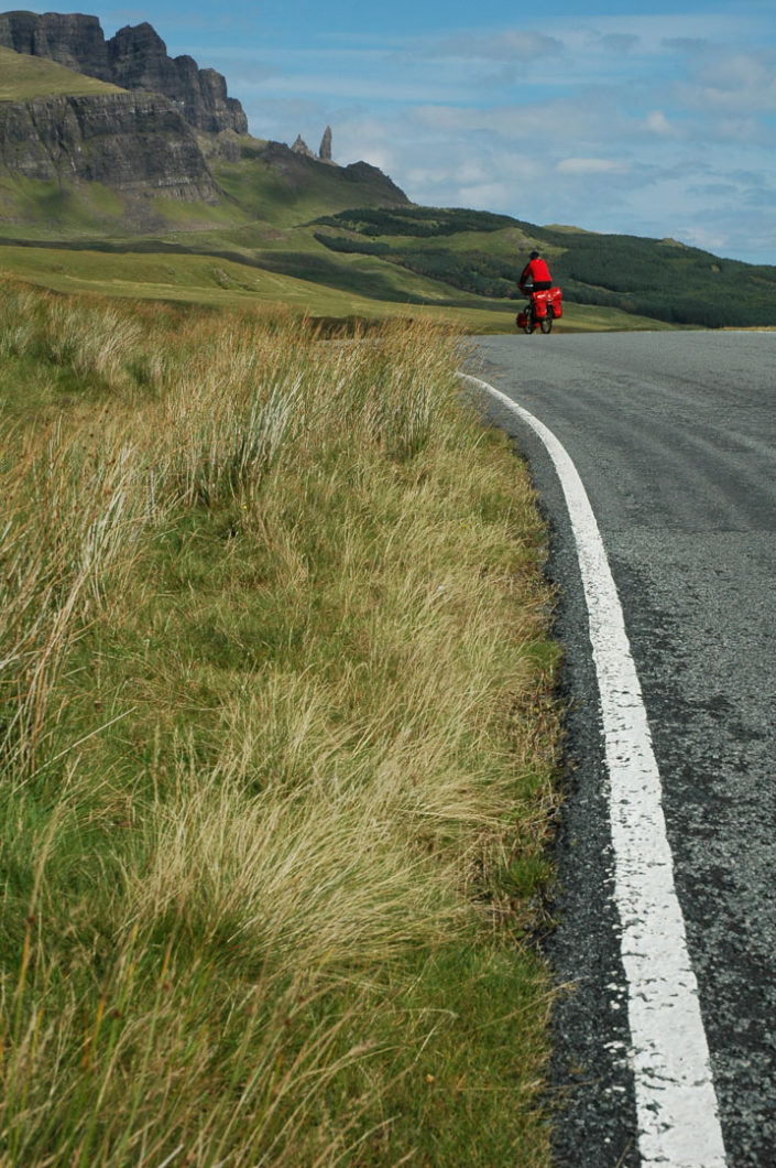 A touring cyclist heads up a hill in Scotland.
