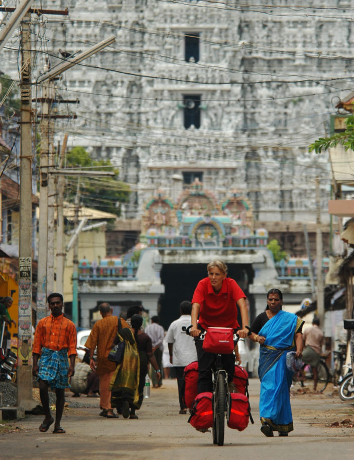 A western cyclist bicycles through an Indian street. In the background a South Indian temple – gopuram can be seen.