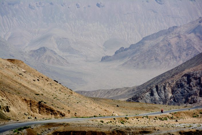 A little red cyclist heads down the Pamir highway.