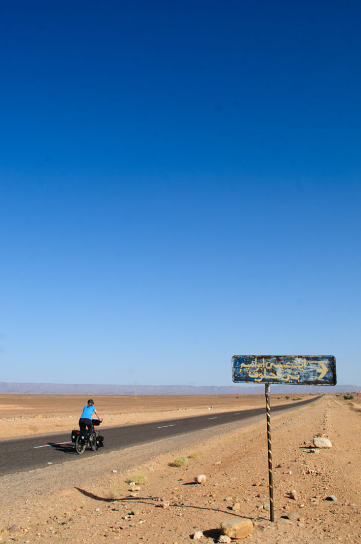 A blue cyclist heads into the desert in Southern Morocco