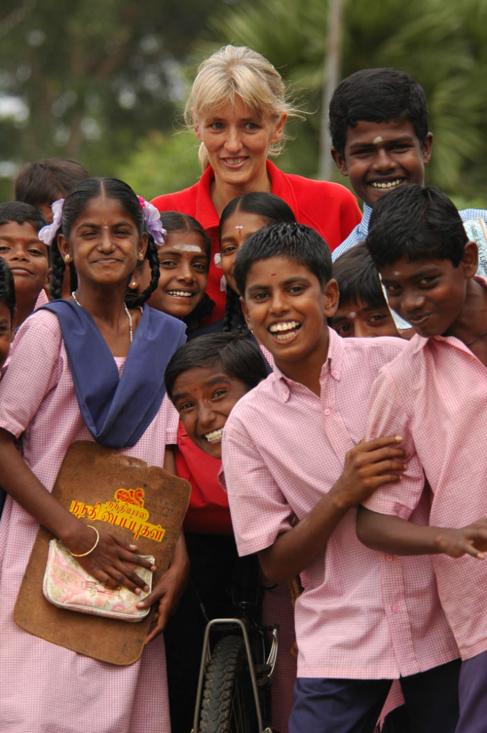 Cyclist is surrounded by friendly schoolkids in India.