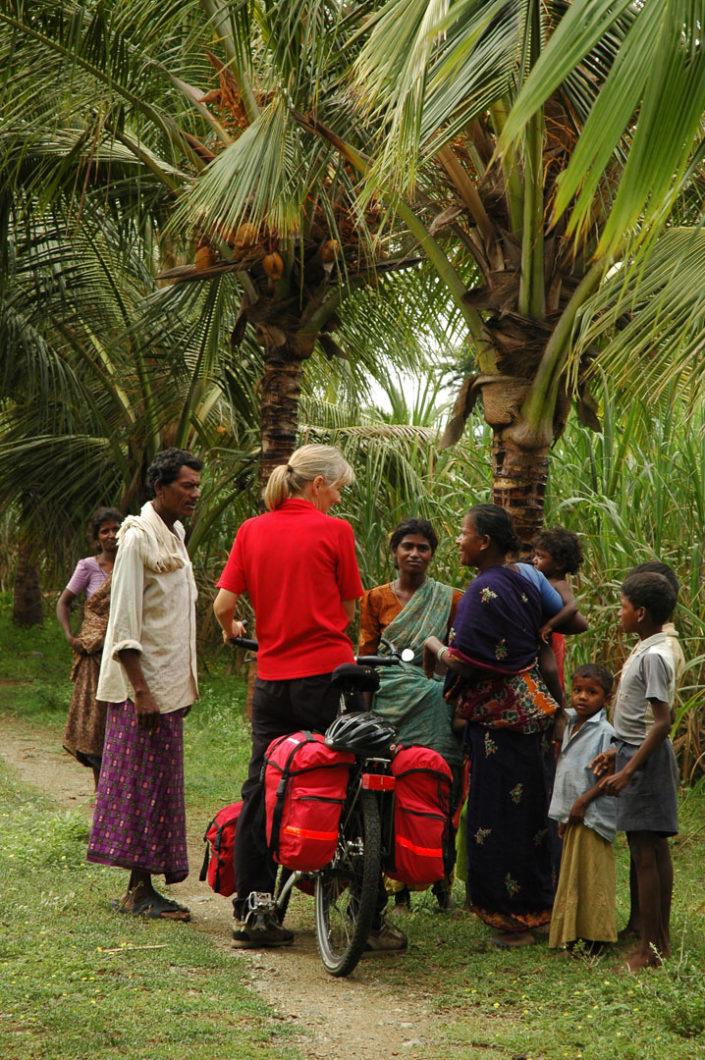 A western touring cyclist is asked questions by friendly locals in South India.