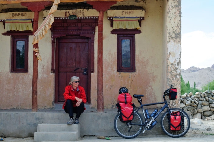 A cyclist sits on the steps of a Monastery in Ladkah.