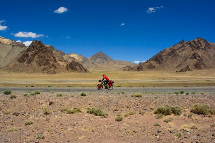 A red cyclist rides the Pamir highway with multicolored mountains behind them.