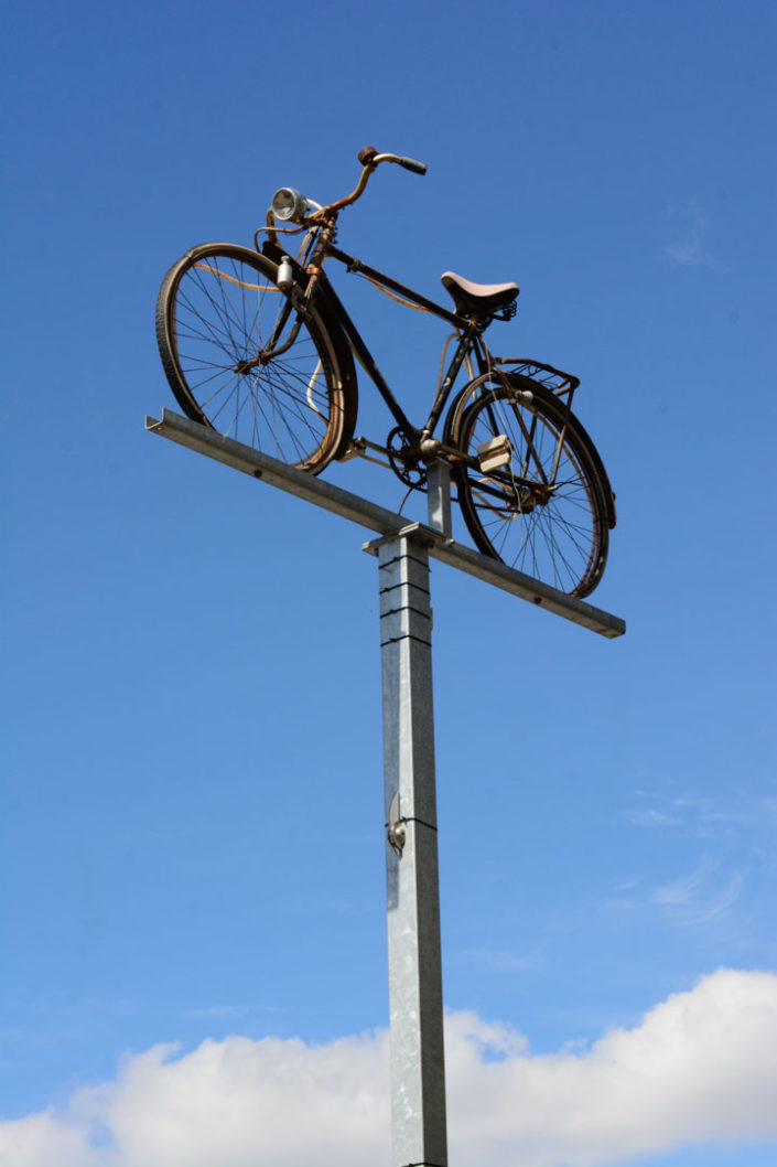 A bicycle stands on top of a high pole in Amsterdam