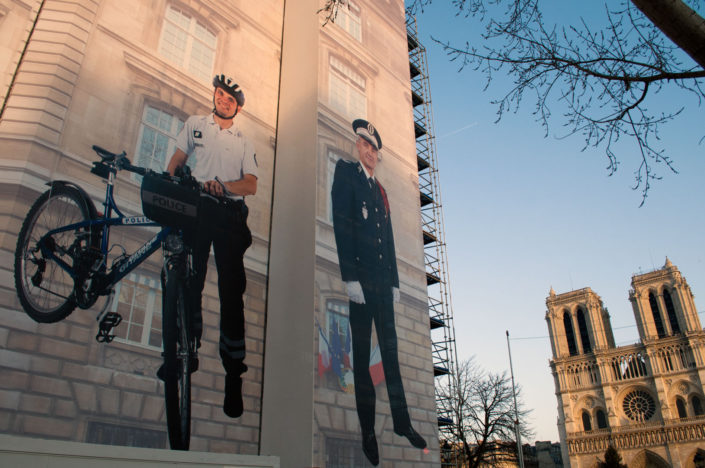A policeman stands with a bicycle on a huge mural in Paris