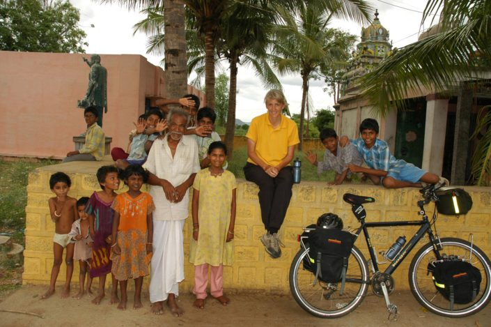 A western cyclist sits on a wall in South India and locals stand next to her.