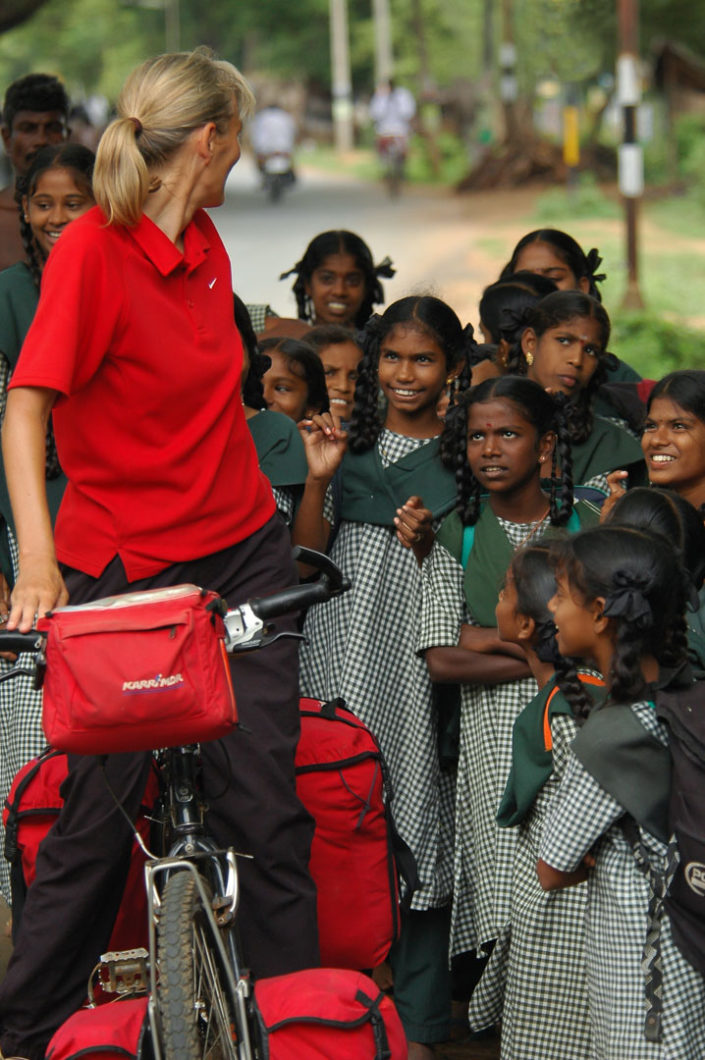 Curious Indian schoolgirls question a female western bicyclist during her bicycle tour of Southern India.