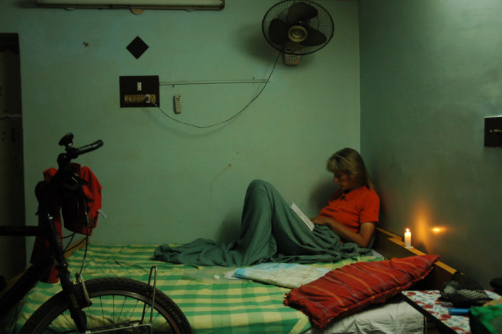 A Western cyclist sits on a hotel bed with a lighted candle in India.