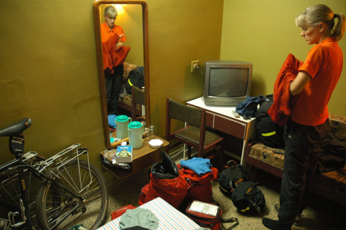 A touring cyclist stands in an Indian hotel room.
