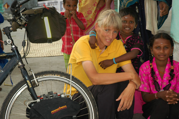 A Western cyclist meets local kids in India.